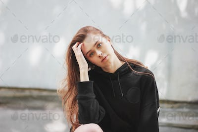Candid portrait of young beautiful long hair girl fashion model hipster in black hoodie