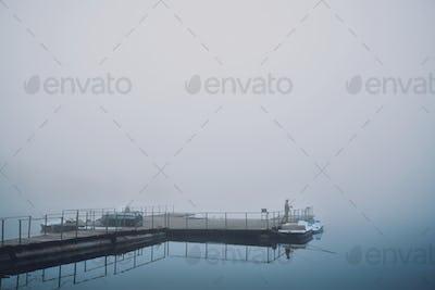 Morning fishing on foggy pond