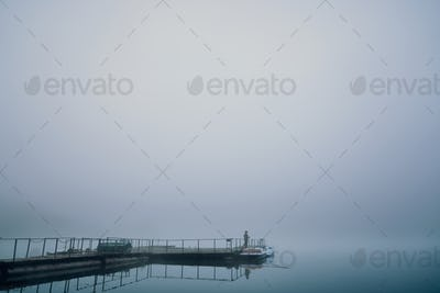 Fisher on wooden berth in foggy morning on lake