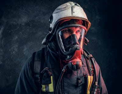 Close-up portrait of a firefighter in safety helmet and oxygen mask.