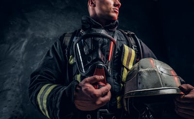 Low angle photo of a man wearing a fire suit holding an oxygen mask and helmet, looking sideways.