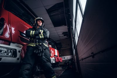 Fireman wearing protective uniform standing next to a fire engine in a garage of a fire department