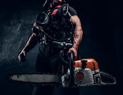 Portrait of muscular man with chainsaw and respirator