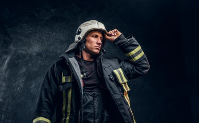 Brave fireman in a fire suit looking sideways and correcting the helmet with his hand