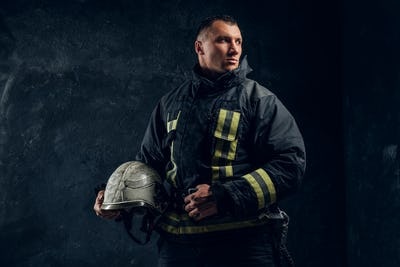 Brutal firefighter looks sideways and holds a helmet in his hand