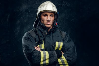 Brutal fireman in uniform posing for the camera standing with crossed arms and confident look.
