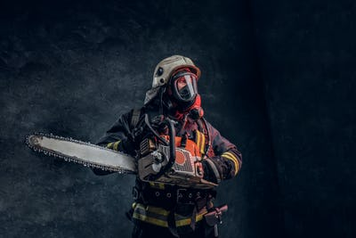 Portrait of a firefighter in safety helmet and oxygen mask holding a chainsaw