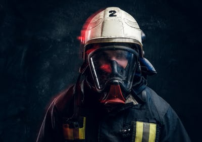 Portrait of a firefighter in safety helmet and an oxygen mask in dark studio