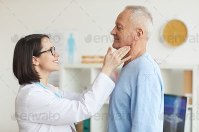 Smiling Female Doctor Examining Senior Man