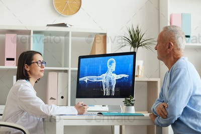 Doctor Talking to Senior Patient in Clinic