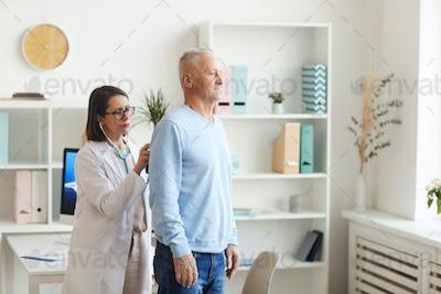 Female Doctor Examining Senior Man