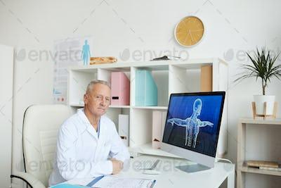 Senior Doctor Sitting at Desk in Modern Clinic
