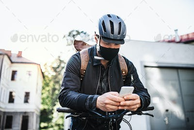 Delivery man courier with face mask and bicycle using smartphone in town