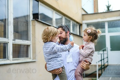 Children greeting father doctor in front of hospital, end of coronavirus