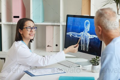 Smiling Doctor Talking to Senior Patient in Clinic