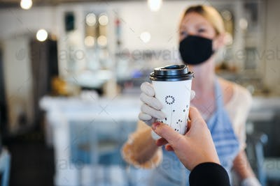 Woman with face mask serving customer, shop open after lockdown quarantine