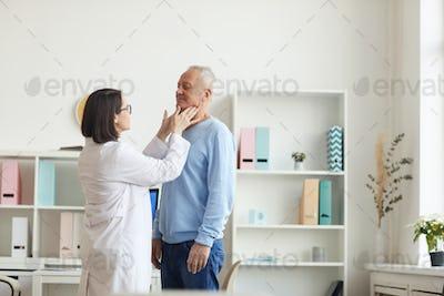 Female Doctor Examining Senior Man during Consultation