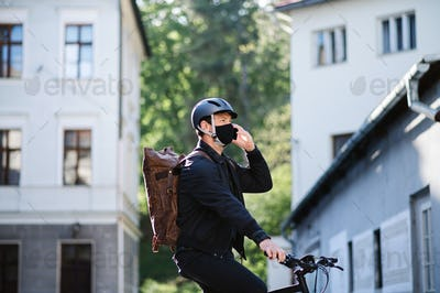 Delivery man courier on bicycle with face mask and smartphone delivering in town