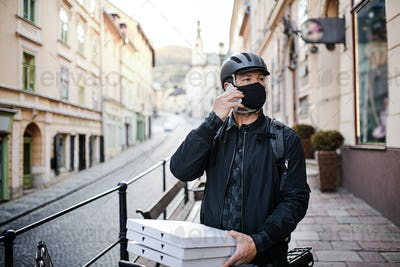 Delivery man courier with smartphone and face mask delivering pizza in town