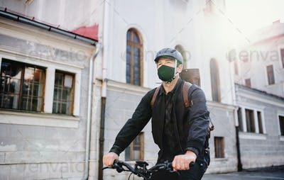 Delivery man courier with face mask and bicycle cycling in town