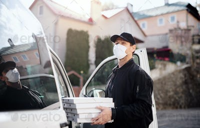 Delivery man courier with face mask delivering pizza in town