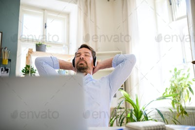 Mature businessman with headphones and laptop indoors in home office, resting