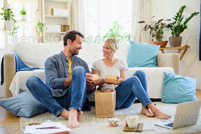 Happy couple sitting on floor indoors at home, eating hamburgers