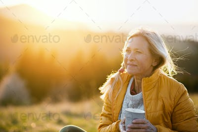 Attractive senior woman sitting outdoors in nature at sunset, relaxing with coffee