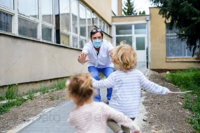 Children running towards doctor in front of hospital, father trying to stop them
