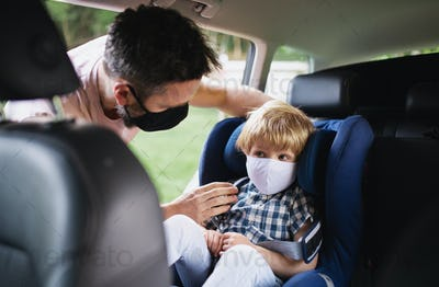 Father putting small son in car seat before trip, wearing face masks