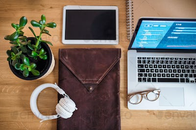 Top view of tablet, laptop, headphones and potted plant on desk