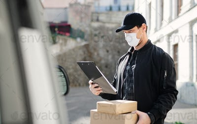 Delivery man courier with face mask delivering parcel box in town