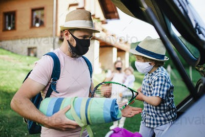 Family with two small children loading car for trip in countryside, wearing face masks