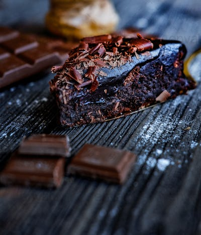 Gourmet slice of melty brownie  and peaces of chocolate on the black table