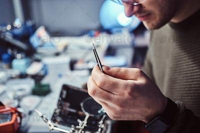 Electronic technician mending a broken phone