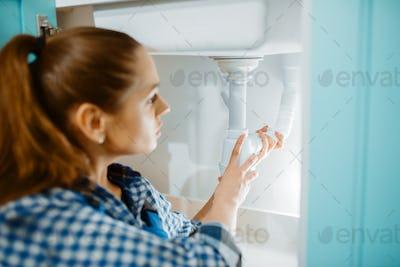 Female plumber in uniform installing drain pipe