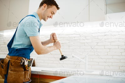 Male plumber in uniform holds plunger, clog