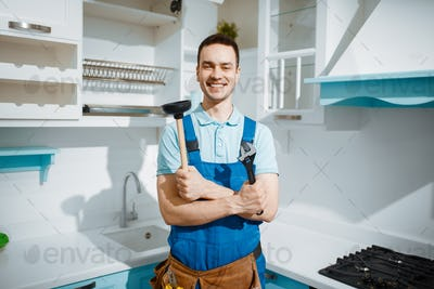 Cheerful male plumber holds wrench and plunger