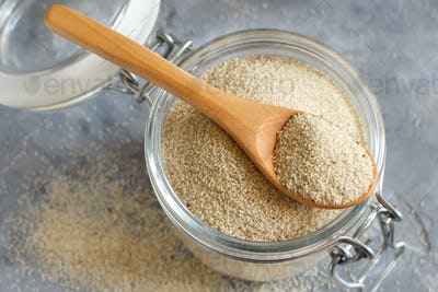Raw uncooked fonio seeds in a glass jar with a spoon on grey background