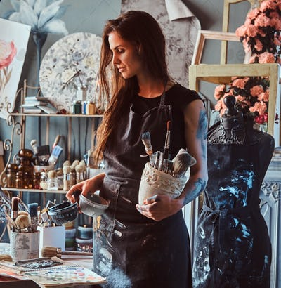 Young artist is tidying up after long working day in her own studio