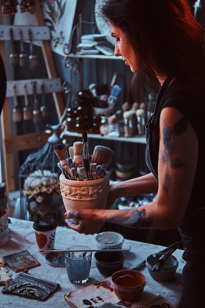 Young attractive painter is holdind jar with brushes in her own cozy workshop