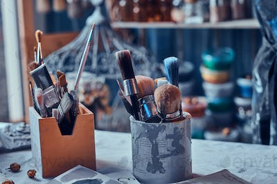 A lot of different brushes on artist's table in jars. There are artistick's mess on the table