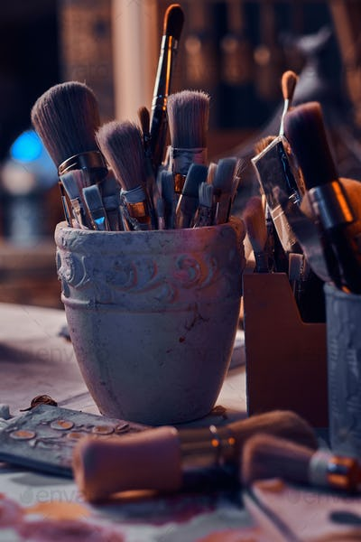 A lot of different brushes on artist's table in jars. There are artistick's mess on the table.