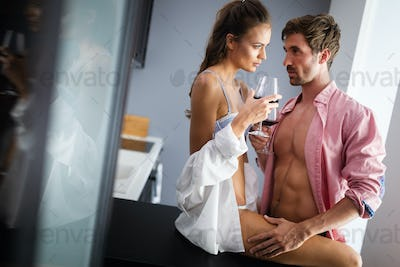 Happy couple enjoying sensual foreplay in kitchen