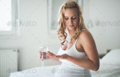 Beautiful pregnant woman taking pills for nausea
