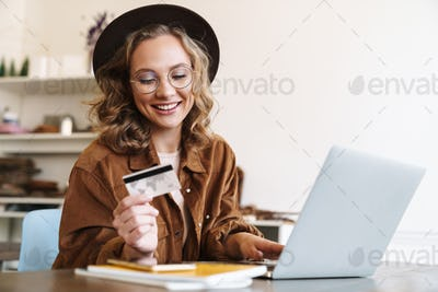 Image of happy young woman working with laptop and holding credit card