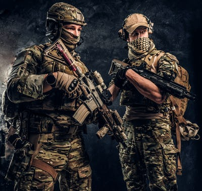 Two special forces soldiers in full protective equipment with assault rifles