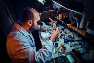 Serious watchmaker  is repairing cutomer's order at his own repairing studio