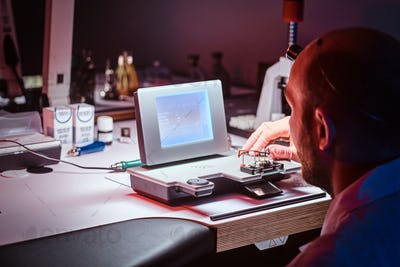 Focused watchmaker is working at his own studio.