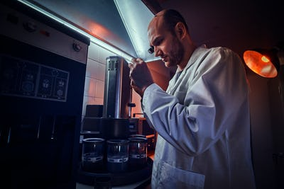 Expirienced watchmaker is working with autoclave at his own studio